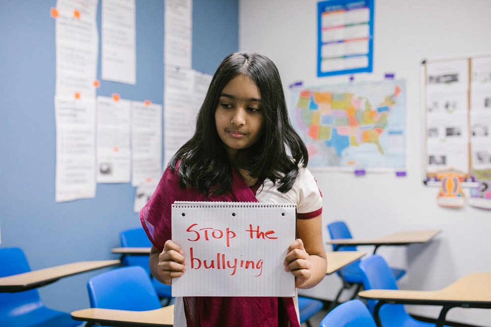 girl holding stop the bullying sign